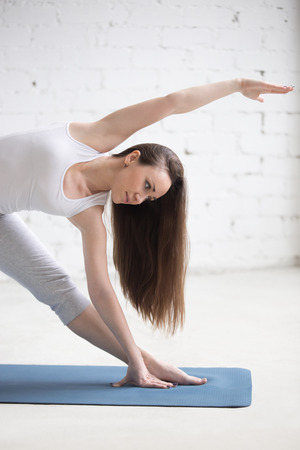 trikonasana: Attractive serene young woman working out indoors. Beautiful model doing exercises on blue mat in room with white walls. Extended Triangle pose, Utthita Trikonasana. Close-up. Vertical image Stock Photo