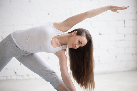 trikonasana: Attractive cheerful young woman working out indoors. Beautiful model doing exercises in room with white walls. Extended Triangle pose, Utthita Trikonasana. Closeup. Horizontal image