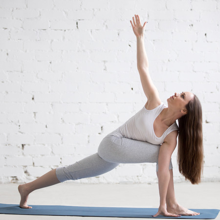 parsvakonasana: Attractive happy young woman working out indoors. Beautiful model doing exercises on blue mat in room with white walls. Twisting Side Angle Pose, Parivrtta Parsvakonasana. Full length. Square image Stock Photo