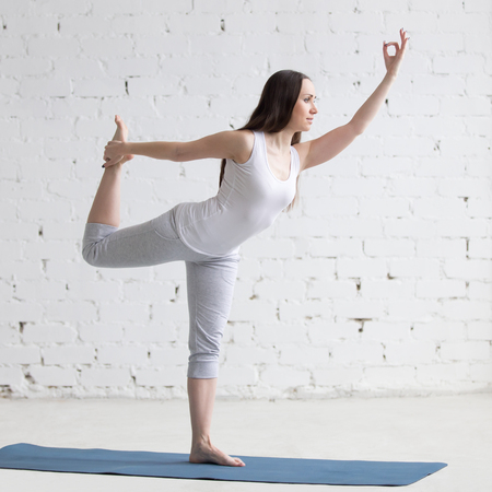 dhanurasana: Attractive happy young woman working out indoors. Portrait of beautiful model doing yoga exercise on blue mat. Natarajasana, Lord of the Dance, King Dancer Pose. Full length. Square image