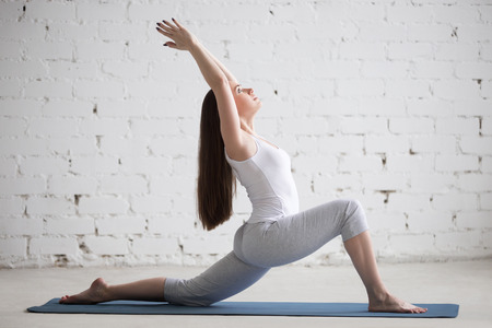 Attractive happy young woman working out indoors. Beautiful model doing exercises on blue mat. Standing in low lunge exercise (horse rider or ashwa sanchalasana pose). Full length. Side view