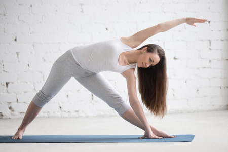 utthita: Attractive cheerful young woman working out indoors. Beautiful model doing exercises on blue mat in room with white walls. Extended Triangle pose, Utthita Trikonasana. Full length. Horizontal image