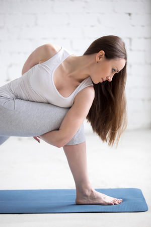 revolved: Attractive happy young woman working out indoors. Beautiful model with long hair doing exercises on blue mat in room with white walls. Revolved Side Angle Pose. Close-up. Vertical image Stock Photo