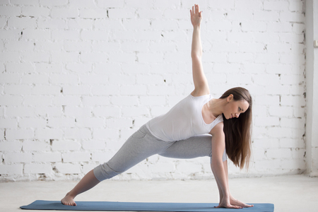 parsvakonasana: Attractive cheerful young woman working out indoors. Beautiful model doing exercises on blue mat in room with white walls. Extended Side Angle Pose, Parsvakonasana. Full length