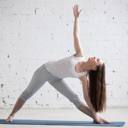 utthita: Attractive cheerful young woman working out indoors. Beautiful model doing exercises on blue mat in room with white walls. Extended Triangle pose, Utthita Trikonasana. Full length. Square image