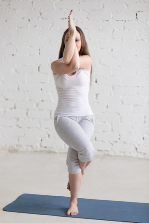 Attractive young woman working out indoors. Beautiful model doing exercises on blue mat in room with white walls. Eagle Pose, Garudasana. Full length. Vertical shot