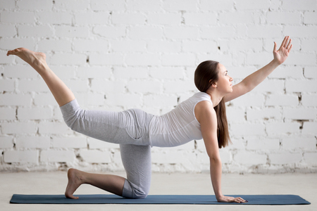 toning: Attractive young woman working out indoors. Beautiful model doing exercises on blue mat in room with white walls. Pilates Bird-dog or Donkey Kick exercise (chakravakasana). Full length
