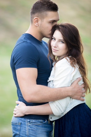 snuggling: Handsome guy gently embracing his girlfriend, kissing her hair, portrait of beautiful young couple on a date wearing casual clothes, hugging, snuggling together in park Stock Photo