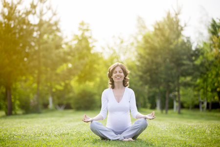 prenatal: Portrait of young pregnant model working out in park. Smiling future mom expecting child sitting cross-legged and meditating with closed eyes outdoors. Prenatal Yoga. Copy space