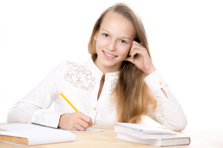 school teens: Portrait of happy beautiful casual girl wearing white shirt, sitting at the desk, doing homework, studying, friendly smiling, looking at camera, studio isolated, white background