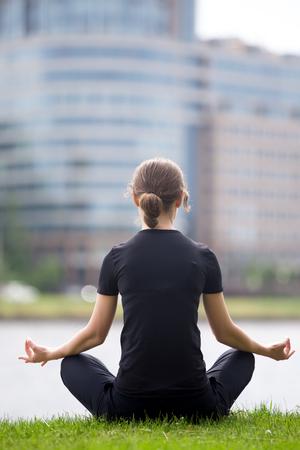 sukhasana: Young office woman sitting cross legged on the street in front of modern office building, meditating, practicing yoga Easy Pose, Sukhasana, asana for meditation, pranayama, breathing, back view