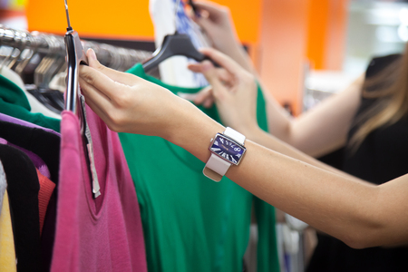 blouses: Two young beautiful women shopping together, standing in the mall, choosing new clothes, holding hangers with different red and green casual blouses, deciding on color, close-up of hands