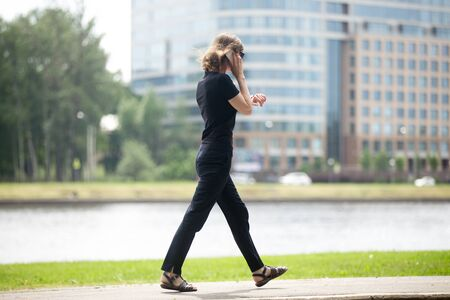 running late: Young business woman running late, walking at fast speed, looking at wristwatch, talking on smartphone on the city street in front of blue glass modern office building, full length