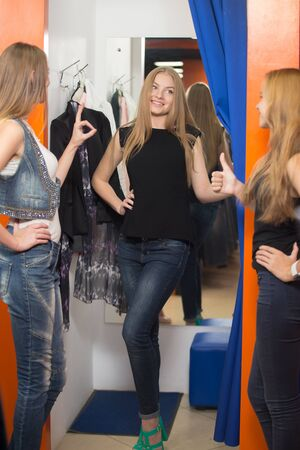 approving: Group of three girlfriends shopping together. Happy smiling young beautiful woman wearing jeans standing in fitting room in mall, trying casual clothes, friends approving new outfit, showing thumbs up