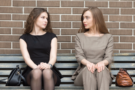 waiting glance: Portrait of two beautiful young female rivals sitting side by side on bench and looking at each other with challenging expressions. Attractive caucasian office women ready for confrontation