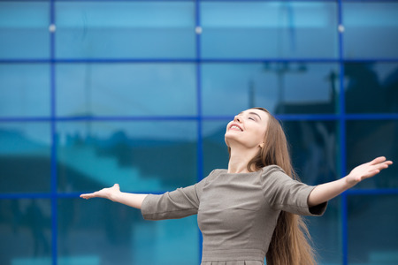 Portrait of cheerful young business woman standing with outstretched arms and relaxing outdoors with closed eyes. Happy beautiful caucasian woman feeling ecstatic on the street in summer. Copy space