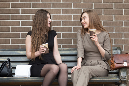break fast: Portrait of two beautiful young girlfriends sitting on bench outdoors and talking with happy smiles. Successful attractive women friends holding paper cups of coffee and chatting during break time Stock Photo