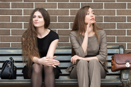 grudge: Full length portrait of two beautiful young female rivals sitting side by side on bench. Attractive caucasian office women holding grudge against each other Stock Photo