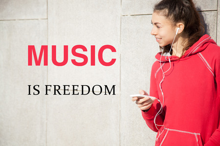 people listening: Portrait of young happy beautiful female resting after everyday workout. Woman athlete runner taking a break and listening to music using phone app. Motivational phrase Music is freedom Stock Photo
