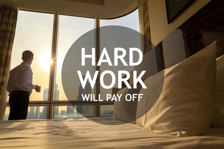 stay home work: Maid-up bed in cozy room. Young businessman with coffee cup standing at window looking at city scenery on the background. Motivational text Hard work will pay off