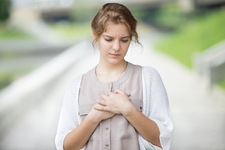 Portrait of stressed beautiful woman walking on the street and touching her chest with sad expression or having heart ache. Attractive model suffering from pain outdoors in summer park