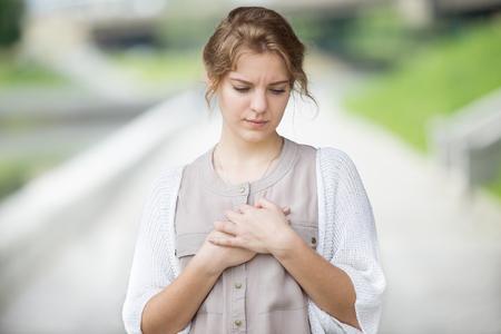 dolor de pecho: Retrato de recalcado hermosa mujer caminando en la calle y tocar su pecho con expresión triste o tener dolor de corazón. Modelo atractivo que sufren de dolor al aire libre en el parque de verano