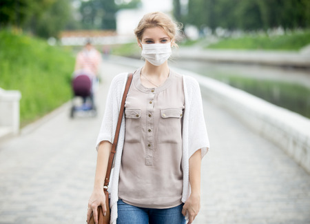 Portrait of beautiful woman walking on the street wearing protective mask as protection against infectious diseases. Attractive unhappy model with flu outdoors. Incidental people on the background Foto de archivo
