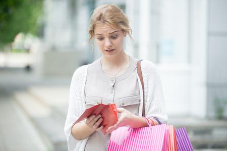 Portrait de malheureux souligné belle personne regardant dans le portefeuille ouvert avec l'expression choquée tout en maintenant la couleur des sacs à l'entrée du centre commercial. Jeune modèle dépensé trop d'argent pendant le temps du shopping