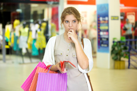 Portrait of thoughtful beautiful person holding open wallet with pensive expression in shopping center with shops on background. Young woman with paper bags deciding on expenses during shopping time Reklamní fotografie