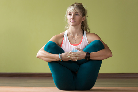 foetus: Sporty beautiful blond young woman in sportswear working out indoors, doing variation of Garbha Pindasana - Womb Embryo Pose on orange eco mat, full length