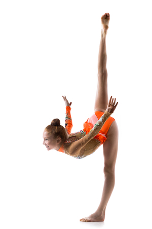 Beautiful happy gymnast athlete teenage girl wearing dancer colorful leotard working out, dancing, posing, doing balance gymnastics exercise, standing splits, full length, studio, white background
