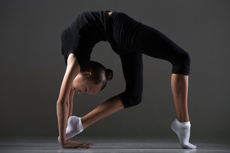 tiptoes: Beautiful cool young fit gymnast athlete woman in sportswear doing art gymnastics, bridge, backward extension acrobatic exercise on tiptoes, full length, studio image, dark background