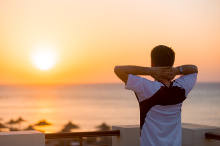 holiday house: Young man standing on the balcony in carefree pose with hands behind his head, enjoying beautiful colorful sunrise or sunset sea landscape and fresh air, copy space, back view