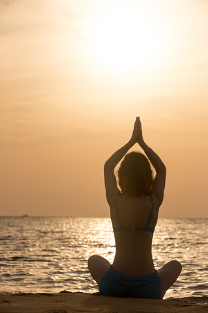 breathe easy: Serene young woman practicing yoga, Sitting on the sea coast at sunset or sunrise in Easy (Pleasant Pose), Sukhasana, hands above head, back view, vertical shot Stock Photo