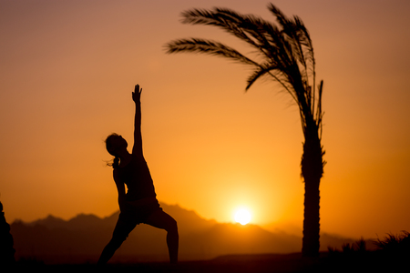 beautiful location: Silhouette of young woman practicing fitness, yoga or pilates at sunset in beautiful location with mountains and palm trees, doing lunge exercise, asana Viparita Virabhadrasana
