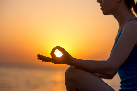 breathe easy: Profile of serene young woman sitting with crossed legs, relaxing on the seashore, meditating with fingers in yogic Jnana mudra, at sunset or sunrise, close up, copy space Stock Photo
