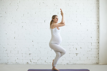 prenatal: Pregnancy Yoga and Fitness concept. Portrait of beautiful young pregnant yoga model working out indoor. Pregnant happy fitness person enjoying yoga practice at home. Prenatal Eagle Pose, Garudasana