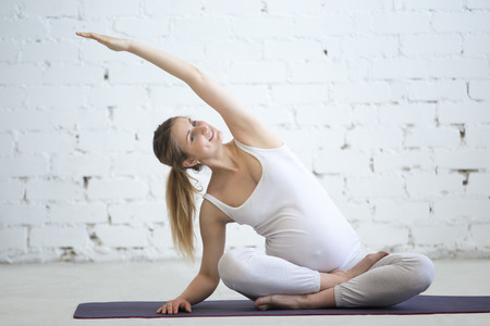 Pregnancy Yoga and Fitness concept. Portrait of young pregnant yoga model working out in loft. Pregnant fitness person practicing yoga at home. Prenatal side bend. Variation of Easy Posture, Sukhasana 스톡 콘텐츠