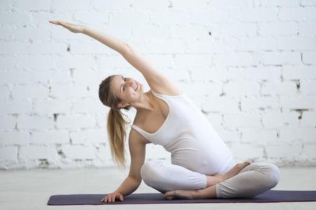 Yoga embarazo y el concepto de fitness. Retrato del modelo de yoga embarazada joven que se resuelve en el desván. Embarazada persona Aptitud practicante de yoga en casa. canto caído prenatal. La variación de la postura fácil, Sukhasana