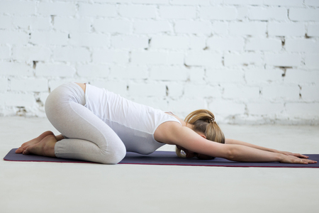 Pregnancy Yoga and Fitness. Portrait of young pregnant yoga model working out in loft with white walls. Pregnant fitness person practicing yoga at home. Prenatal Balasana, Child Pose Banco de Imagens