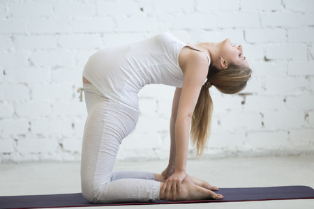 ushtrasana: Pregnancy Yoga and Fitness concept. Portrait of beautiful young pregnant yoga model working out indoor. Pregnant happy fitness person practicing yoga at home. Prenatal Camel pose. Full length