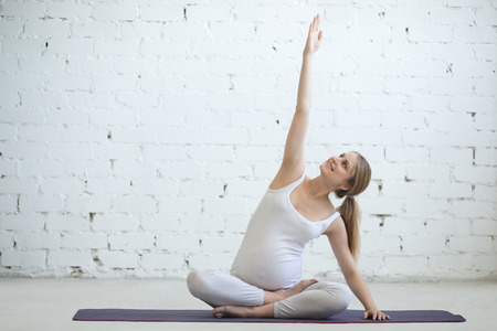 prenatal: Pregnancy Yoga and Fitness concept. Portrait of young pregnant yoga model working out indoors. Pregnant fitness person practicing yoga at home. Prenatal side stretching in position with crossed legs
