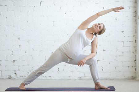 side angle pose: Pregnancy Yoga and Fitness concept. Portrait of beautiful young pregnant yoga model working out indoor. Pregnant happy fitness person enjoying yoga practice at home. Prenatal extended side angle pose Stock Photo