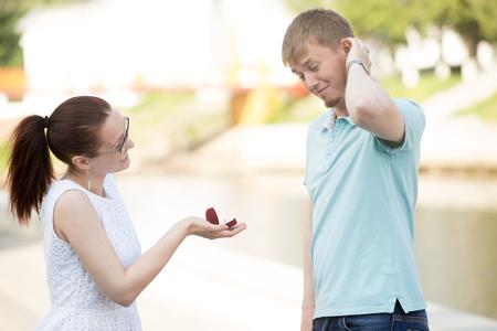 dudando: Bastante joven mujer que solicita la mano de su amado novio en el parque, pidiendo que te cases. niña sonriente sosteniendo caja con anillo de compromiso. Desconcertado joven rascarse la cabeza, pensando qué hacer