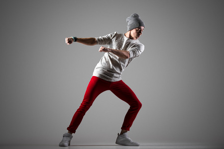 red jeans: One attractive fit young man in casual red jeans working out, dancing. Stylish handsome dancer performing. Full length photo on studio gray background Stock Photo