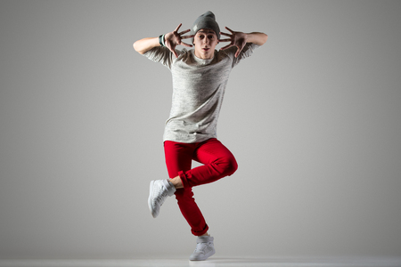 red jeans: One smiling fit young man in casual red jeans working out, dancing. Funny dancer fooling around. Full length photo on studio gray background