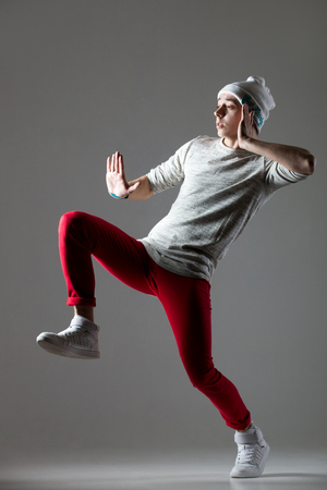 beanie: Portrait of one funny hipster young man dancing wearing casual red jeans and beanie. Cool hip-hop dancer guy working out. Full length photo image on studio gray background Stock Photo