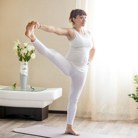 hasta: Healthy Pregnancy Yoga and Fitness concept. Young smiling pregnant yoga woman working out at home. Pregnant happy model doing prenatal Utthita Hasta Padangustasana, Extended Hand to Big Toe yoga pose