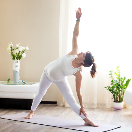 utthita: Healthy Pregnancy Yoga and Fitness concept. Young pregnant yoga woman working out in cozy living room interior. Pregnant model doing prenatal Extended triangle, Utthita Trikonasana yoga pose