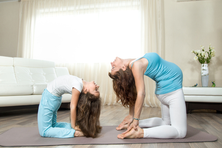 ushtrasana: Family healthy lifestyle concept. Pregnancy Yoga and Fitness. Young happy pregnant yoga mom working out with her little daughter in living room. Pregnant mother and kid exercising at home Stock Photo